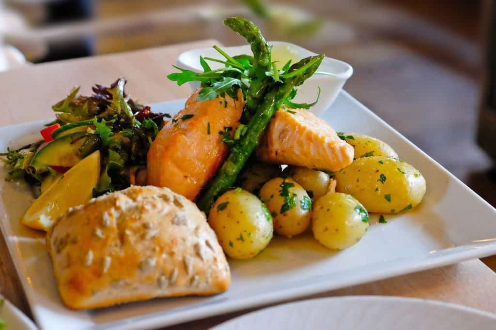 salmon baked with skin removed, served with salad and potatoes